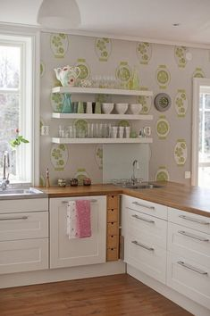 A fehér IKEA konyhabútor nagyszerű kiegészítője a tölgy munkapult és a kellemes, mintás tapéta: