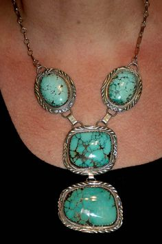 "Posted as ""Sterling and Turquoise Necklace by Zuni Artist Sensa Eustace""  Eustice family family work typically has carved stones and curved feathers. This looks like Navajo work."