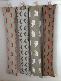 Draught excluders in Emily Bond Dairy Cow and Dachshund fabrics