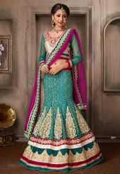 Epitomize the timeless elegance of a bride adorning this exclusively designed Teal Blue Net Lehenga. The Semi-stitched ensemble has a Faux Crepe Lining. Featuring a mermaid silhouette, this stunning ensemble lends you a slender look. Elaborate Resham, Golden Zari and Stone work, depicting Floral and Ornamental motifs adorn the attire. Its panels are further enhanced with Beads and Dori embroidered Applique work. As shown, an Off White and Teal Blue Art Silk Jacquard and Net embroidered…