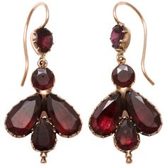 Georgian gold and garnet earrings c. 1820 are 15kt gold with foiled garnets. The form, an unusual shape, looks more like an insect than it does the floral form of small garnet earrings we see more often. As there was no electricity at this time, jewelers foiled gemstones and semi precious stones with a sliver of metal or foil material behind the stones to catch and reflect the available light. Circa 1820