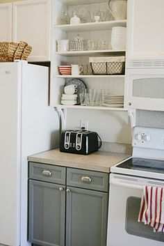 Removing cupboard doors creates open shelves. Painting the back the same color as the lower cabinets.