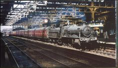 The typical iron and glass train shed, seen here spanning the platforms at Birmingham Snow Hill in 1961, is one of the classic features of the city station. On a sunny day Western Region locomotive no. 7330 brings its long train to a gentle halt.