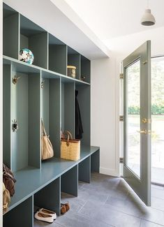 A glass paneled gray door with a brass handle opens to a mudroom boasting a gray bench fixed beneath gray open lockers fitted with gold bunny hooks mounted beneath gray shelves. Room, Mudroom, Grey Doors, Home, Mudroom Design, Mudroom Lockers, Small Laundry Room Organization, Room Storage Diy, Mudroom Cubbies
