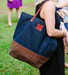 A classic tote made from rugged materials, this canvas bag can handle heavy-duty use. The body is sewn from hand-waxed canvas in two tones, combined with sturdy leather straps and finished with copper rivets.