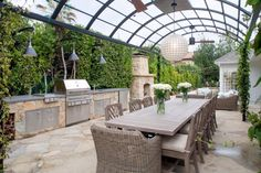 This spectacular backyard boasts a state-of-the-art outdoor kitchen with stone counters and a long, neutral dining table that makes it ideal for entertaining. Greenery surrounds the perimeter of the space and ivy hangs from a contemporary metal pergola that supports wood ceiling fans and a paper lantern, which offers a soft glow above the dining table.