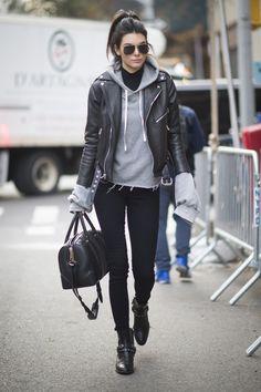 black sunglasses, black shirt underneath light grey hoodie sweatshirt, black leather jacket over, black skinny jeans, black ankle boots and a black handbag.
