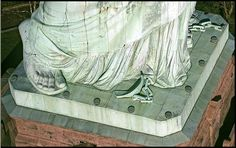 Statue of Liberty's feet and broken chains  - Freedom is not standing still. A symbolic feature that people cannot see is the broken chain wrapped around the Statue's feet. Protruding from the bottom of her robe, the broken chains symbolize her free forward movement, enlightening the world with her torch free from oppression and servitude.