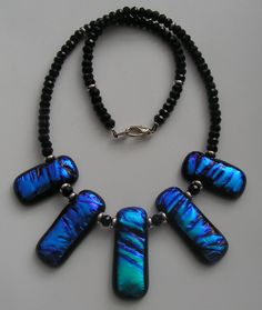 Necklace made using 5 turquoise-blue slide pendants and a combination of sterling silver findings and jet black crystal beads.Made in November 2014 and sold in my Exhibition in December 2014. Unique Glass Art by Marion.