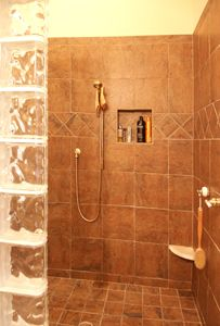 Master Bath    - Shower stall built without door or ledge with drainage floor for easy access via wheelchair  - Controls set low and away from shower head for safe testing of water temperature  - Removable shower head for adjustable heights
