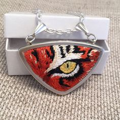 """If eyes are the windows to the soul, the eye of the tiger holds the secrets to this wild feline. Hand embroidered in great detail, this silver triangular pendant necklace features an orange and black striped tigers eye on 100% pure white wool felt.  🌴 SPECIFICS:  -Pendant is a triangle with two bails -Size: 2"""" x 1.25"""" or 50mm x 32mm -Chain: your choice of a 16 or 18 silver cable chain  Check out my other animal necklaces…"""