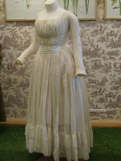 Chemise gown from the late 1780's with tight sleeves with buttons at the cuff, a triple row of drawstrings across the torso, and a ruffle at the hem.
