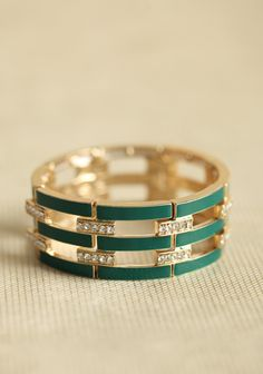 Eunomia Rhinestone Bracelet, gold-toned stretch bracelet features hunter green stripes and sparkling rhinestone accents.
