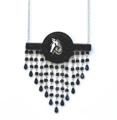 """Collier zèbre """"passe muraille"""" : une figurine de zèbre, un cadre baroque, une barre allongée en résine à laquelle est accroché un rideau de perles de verre et de résine. De l'élégance et un brin de folie, à voir ici : http://bijoux-animal.com/colliers/duchesse/collier-zebre-passe-muraille-detail"""