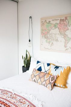 Bohemian textiles, vintage map as wall art, and a mounted light bulb pendant