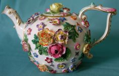 "A Late 19th century Meissen flower-encrusted teapot c.1880 The teapot and cover with encrusted roses and painted with scattered insects,blue crossed swords and number 16 impressed 4""(10cm) tall x 6"" (15.5cm) from spout to handle."