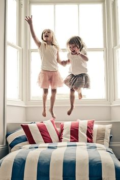 Sibling photography girls sisters jumping on the bed action lifestyle
