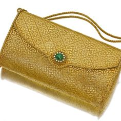 Property of a New York Lady An eighteen karat gold, emerald and diamond handbag, Van Cleef & Arpels the envelope shape purse of woven mesh design with a hinged lid enhanced by an oval emerald cabochon, measuring approximately 11.95 x 10.00mm., within a bi-colored gold wire surround, enhanced by circular-cut diamonds, opening to reveal a mirror, suspended from rope chain handles; signed Van Cleef & Arpels; gross weight approximately: 398.1 grams; dimensions: 6 3/4 x 4 x 2in.; handle length…