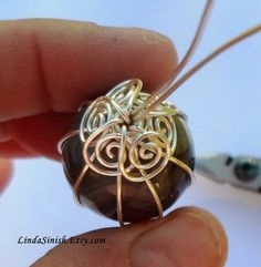 Artyzen Studio by Linda Sinish: Wrapping a Marble Pendant - Free Tutorial 4 wires bound with a 1/2 round wrap. Wires brought up, wrapped at the top, 6 coiled as shown and a bail made from the other 2. Form a round bail at the top and coil the ends wrapping above the coils below the bail.