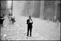 A man picks up a paper that was blown out of the towers after the attack of the World Trade Center on Sept. 11, 2001.