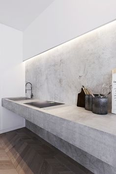 Kitchen: super thick concrete bench/counter, concrete wall/splashback, induction cooktop, chevron wooden floor