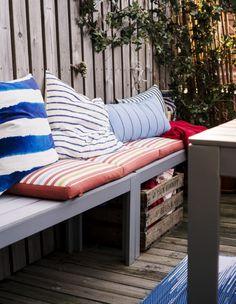Rząd drewnianych ławek z poduszkami, a pod spodem skrzynka z poduszkami i kocami.