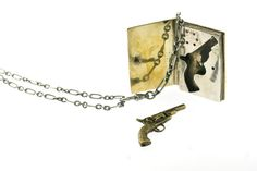 The Law in Six Parts Locket is a minature book that opens to reveal a revolver and 5 bullets hidden with the pages.