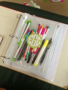 Monogrammed decal on a binder pouch w/ pens, highlighters, and pencils.