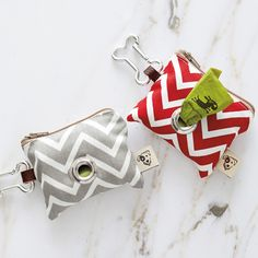 """Doggie Pick-Up Pouch (The Container Store) (""""Pick up after your four-legged friend in style with our Chevron Doggie Pick-Up Pouch! Its cute pattern holds two standard rolls of pick-up bags and its dog bone-shaped carabiner makes it easily portable no matter where you and your pup go!"""" /// 3 1/2"""" x 1"""" x 3"""" H /// Available in Red & White or Grey & White.)"""