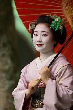 The maiko Shouko holding a umbrella. Please notice the little birds on her june kanzashi! (Source)