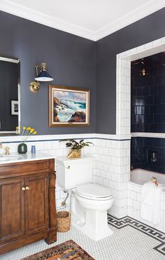 The use of wood and ceramic is beautiful here. The navy is a little dark for a bathroom but the high contrast of the clean white tile floor and walls keep it feeling bright and clean.