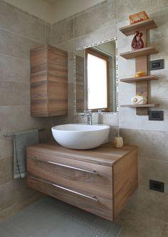 Ambientazione del mobile bagno su misura in noce nazionale segato, composto da cassettoni e vano sospesi e mensole.