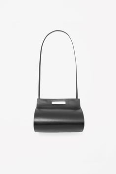 A modern style with rounded proportions, this bag is made from smooth panels of moulded leather. With a detachable leather shoulder strap and simple cut-out handle, it has a lined interior compartment, smaller inside zip pocket and a hidden magnetic fastening.