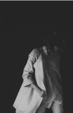 Gene Doe. who is she in the shadows. coat bundled. dark messy bun turned away. subtle hand on collar. black and white fashion of this woman so shy