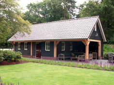 1. Zwarte houten schuur met tuinkamer en overkapping en blanke kolommen 64m2