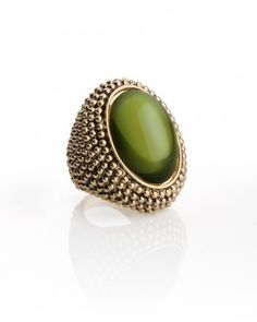 Spark the imagination with our mesmerizing olivine cocktail ring in the season's hottest color. Set with a green glass cabochon stone, the textured base looks regal with its antique gold plating. Headed to a midnight masquerade? Every face might be hidden, but your panache is impossible to conceal.        Wear this with          jewel tones like sapphire, garnet, and deep citrine.         Perfect for          a bal masqué or festive dinner party.
