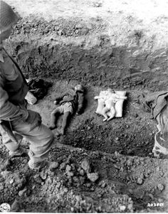 """bag-of-dirt: """" A U.S. Army soldier stands above the corpses of children who died at Mittelbau-Dora concentration camp (also known as Nordhausen concentration camp, a subcamp of Buchenwald concentration camp). As the Allies closed in around the area..."""