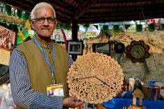 Shilp guru awardee Mahesh Chand displays his well carved wooden watch and replicas of India Gate in the backdrop! India Gate, Wooden Watch, Stalls, Backdrops, Carving, Display, Wooden Clock, Floor Space, Billboard