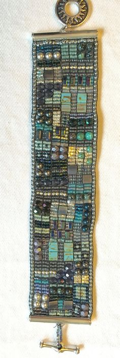 Hand woven bracelet in shades of Blue with various sizes of different style beads woven throughout. Uses 4mm Turquoise beads, 4mm Hematite beads, Czech glass beads, Swarovski Crystals and Pearls, Silver beads, and a variety of Japanese seed beads.  Closure is a silver toggle Overall length is 6 1/4 inches, width is 1 3/8 inch