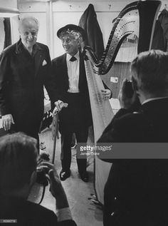 Copnductor Leopold Stokowski (L) and entertainer Harpo Marx (C) posing for pictures.