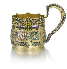 A silver-gilt and cloisonné enamel tea glass holder, Feodor Rückert, Moscow, probably retailed by Fabergé, 1908-1917 the bombé sides with shaded flowers and grape clusters on a hammered surface below a wide geometric border with cloison coils on a green ground, shaped rim, the handle with foliage and scale pattern,