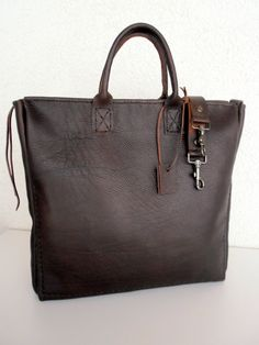 Large dark brown leather bag, in a beautiful natural black color leather.  It comes with a double outside leather pocket, and it has 3 inside pockets in one side of the bag (1 bigger and 2 smaller thinner pockets).This bag includes zipper and crossbody strap.    Simple and stylish.    Premium cowhide, in dark brown color, thick and sturdy, and strong leather straps in the same leather. Raw finish to appreciate this beautiful leather.  This bag is made with hand stichig leather, which makes…