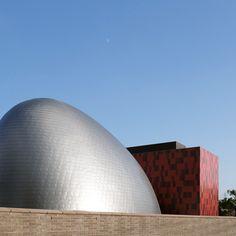 Блоб-образный серебро здания контрастирует с красной башни на японский…