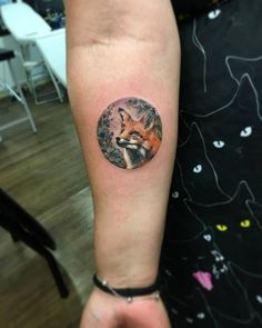 Illustrative fox tattoo on the right inner arm.