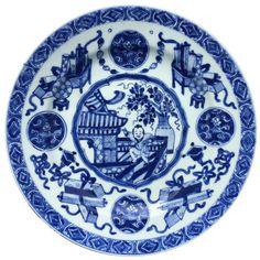 Paire d'assiettes à décor d'un garçon dansant en porcelaine de Chine d'époque Kangxi Peintes dans un vibrant bleu sous couverte, à décor en plein avec au centre un médaillon représentant un garçon dansant dans un jardin devant un vase fleuri. Sur l'aile, des emblèmes bouddhiques et des lotus.