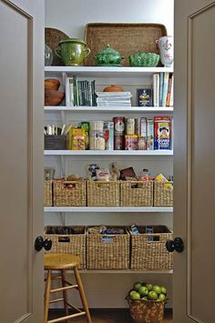 Baskets inside this spacious walk-in pantry store herbs and spices, canned goods, and cooking staples.