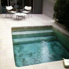 Mini piscine en pierre incrustée dans une terrasse.