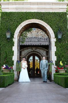 The bride & groom stand outside the gates of Villa Siena under the archway | villasiena.cc