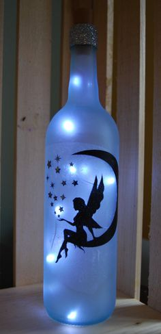 Wine bottle, frosted glass with an a fairy sitting on the moon decoupaged on it. Bottle is filled with clear battery operated mini LED string lights, which make this a unique and beautiful accent piece.