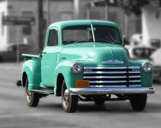 Photo of an early 1950s Chevrolet pickup truck driving down a street in Fredericksburg, Texas. By Terry Fleckney